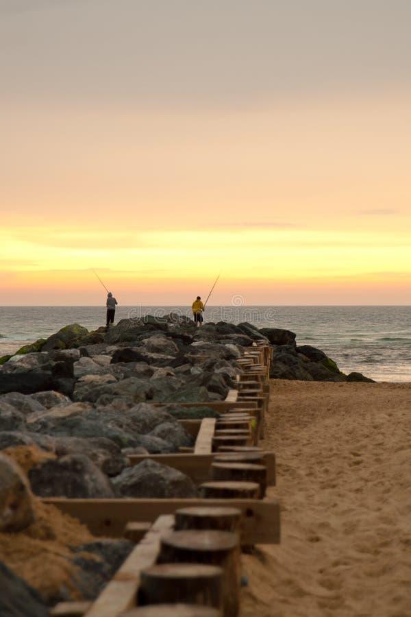 Люди удя на пляже на заходе солнца стоковые фотографии rf