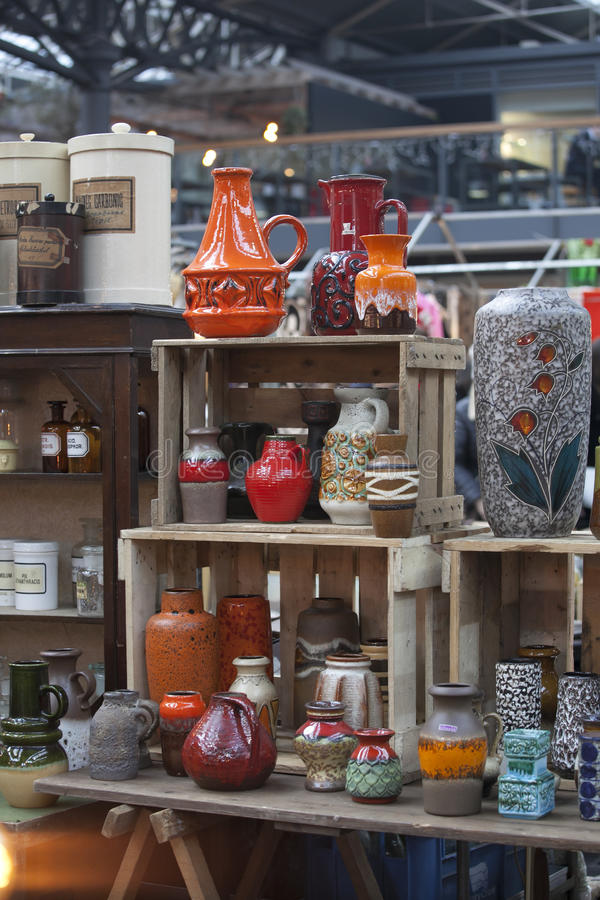 Люди ходят по магазинам на старом рынке Spitalfields в Лондоне Рынок существовал здесь на по крайней мере 350 лет стоковые изображения