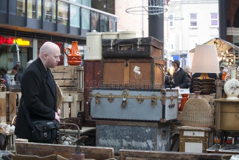Люди ходят по магазинам на старом рынке Spitalfields в Лондоне Рынок существовал здесь на по крайней мере 350 лет стоковое изображение