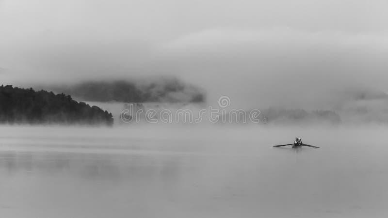 Люди canoeing на зоре стоковые фотографии rf