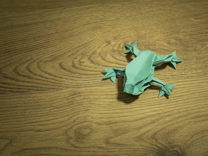Лягушка Origami на деревянной предпосылке стоковые фото