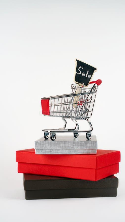 Магазинная тележкаа или вагонетка магазина от супермаркета с продажей знака на подарочных коробках на белой предпосылке, космосе  стоковое изображение rf