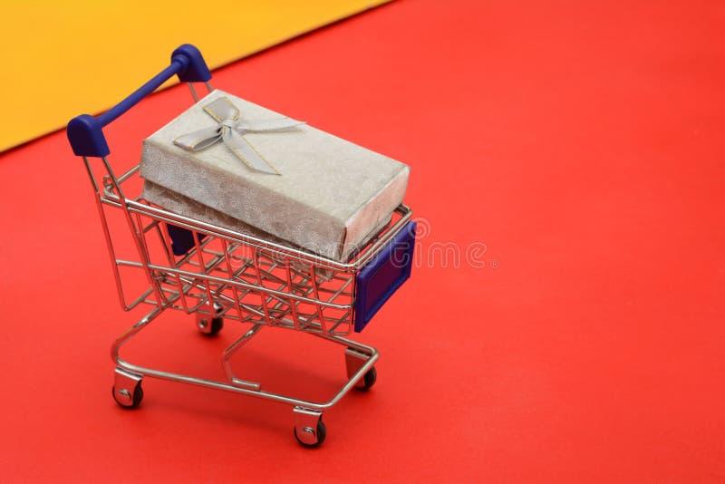 Магазинная тележкаа с подарочной коробкой на красном знамени предпосылки стоковые изображения rf