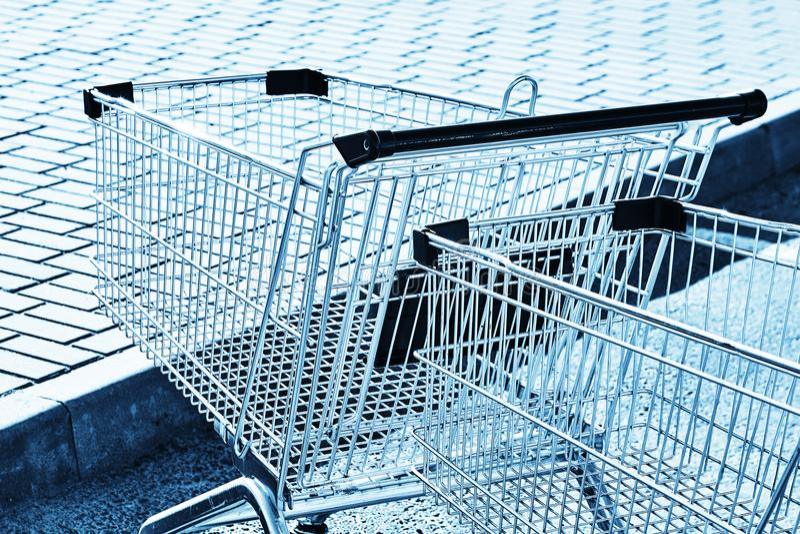 2 магазинной тележкаи в месте для стоянки магазина Голубой тонизировать стоковое изображение