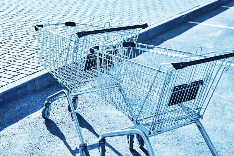 Магазинные тележкаи в месте для стоянки магазина Голубой тонизировать стоковые фотографии rf