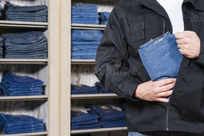Магазинный вор крадя джинсовую ткань стоковое изображение