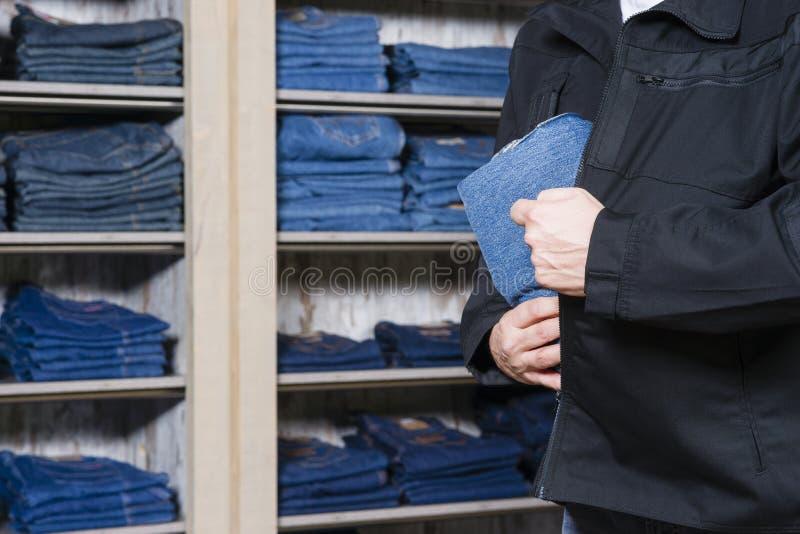 Магазинный вор крадя джинсовую ткань стоковые фото