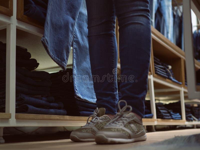Магазин одежд джинсов Девушка ног в джинсах в stor одежды джинсовой ткани стоковая фотография rf