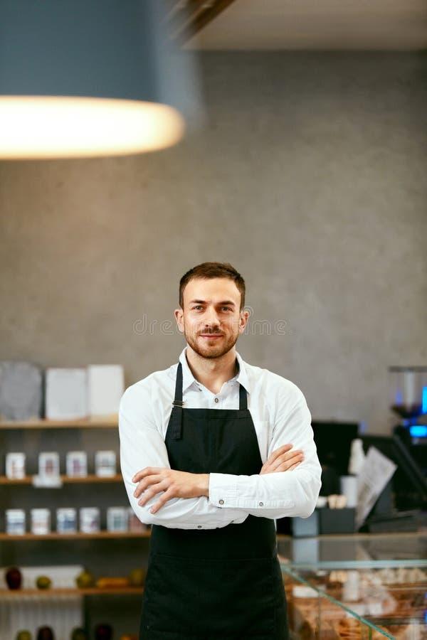 Магазин печенья Портрет молодого человека в магазине хлебопекарни стоковое изображение