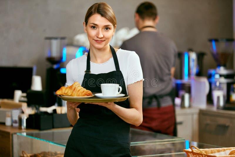 Магазин печенья Портрет молодой женщины в магазине хлебопекарни стоковые фото