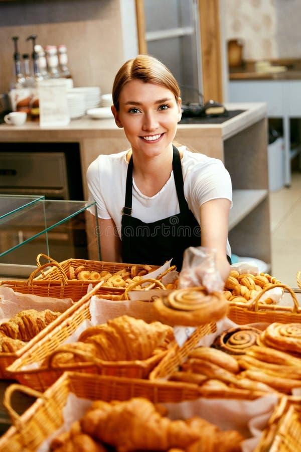 магазин хлебопекарни Счастливая женщина продавая печенье стоковые фото