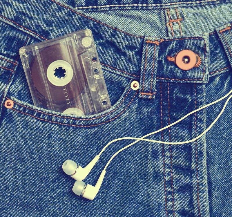 Магнитофонная кассета в кармане старомодных голубых джинсов и headp стоковое изображение rf