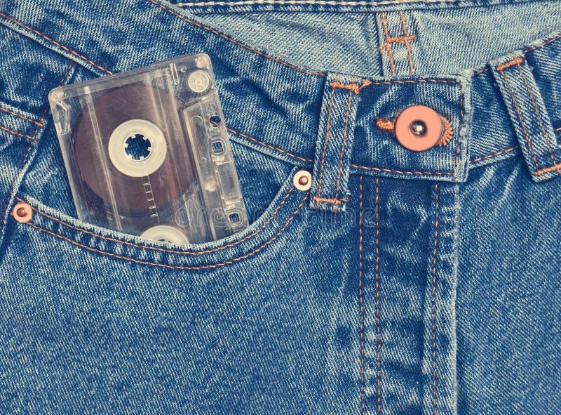 Магнитофонная кассета в кармане старомодных голубых джинсов стоковые фото