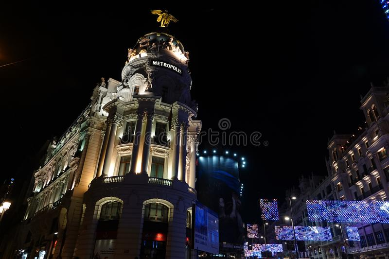 Мадрид, Испания; 6-ое января 2019: Здание метрополии расположенное между Gran через улицу и улицей Alcala загоренной вечером на стоковое изображение