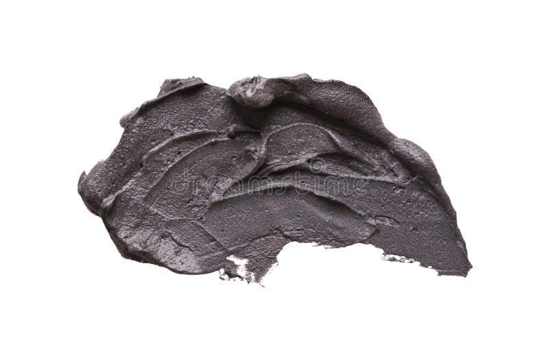 Мазок маски черной глины лицевой на белизне изолировал предпосылку стоковая фотография rf