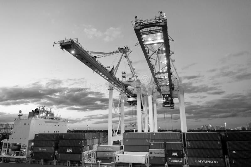 Майами, США - 1-ое марта 2016: краны и грузовые контейнеры штабелированные в порте Порт или стержень контейнера с ночой стоковые фотографии rf