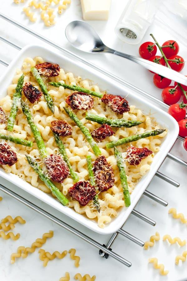 макаронные изделия испеченные с высушенными томатами, спаржей и сыром pecorino стоковые изображения