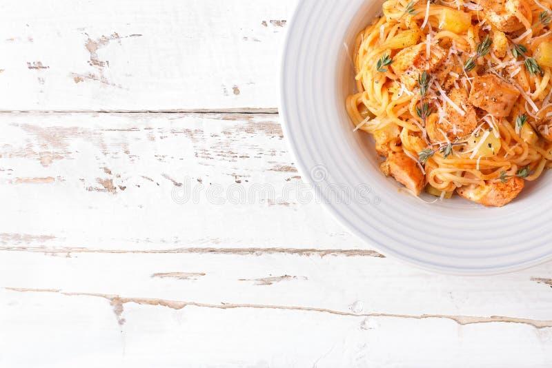 Макаронные изделия спагетти bolognese с томатным соусом, овощами и мясом цыпленка на белой деревянной деревенской предпосылке Тра стоковое фото rf