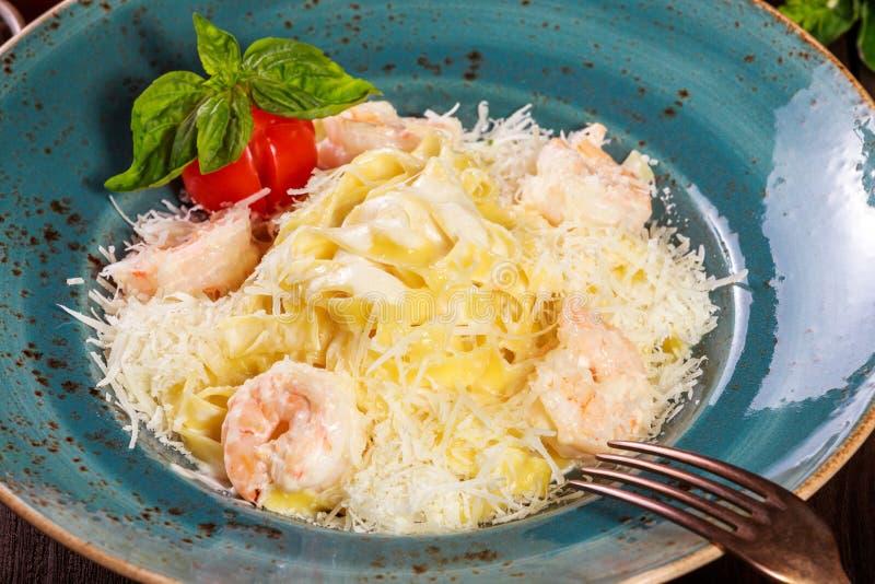 Макаронные изделия с креветкой, пармезаном сыра, томатами, базиликом и cream соусом на темной деревянной предпосылке, итальянской стоковое изображение rf