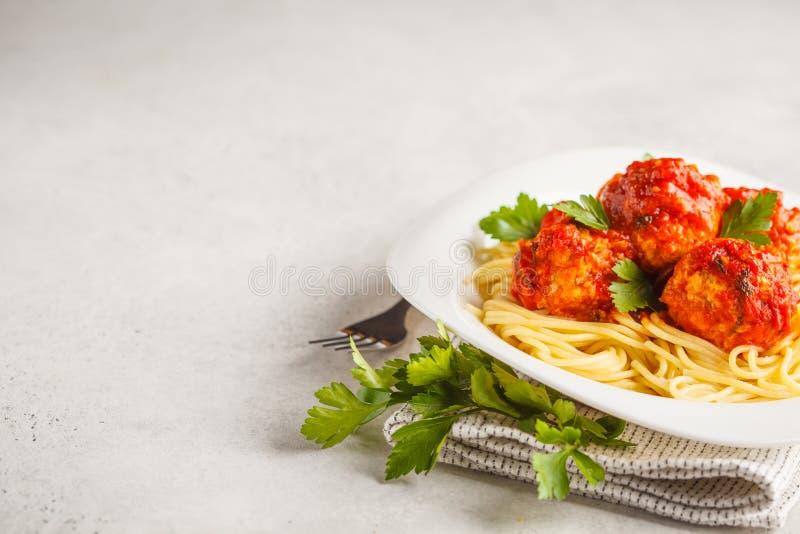 Макаронные изделия с фрикадельками цыпленка в томатном соусе в белой плите, c стоковые фото