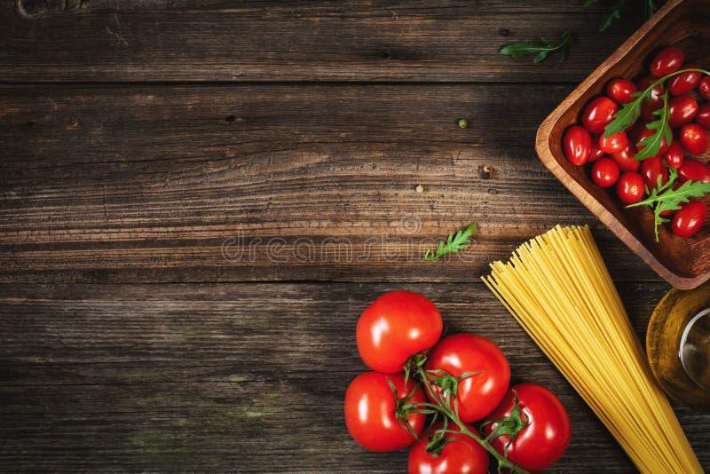 Макаронные изделия, томаты, оливковое масло и травы на деревянной предпосылке стоковое фото