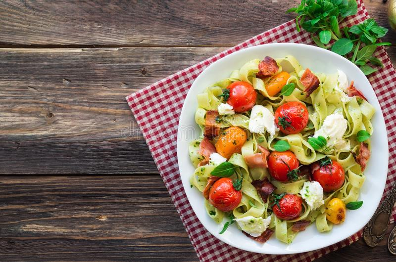 Макаронные изделия Fettuccine с испеченным сыром томатов, бекона и моццареллы стоковое изображение rf