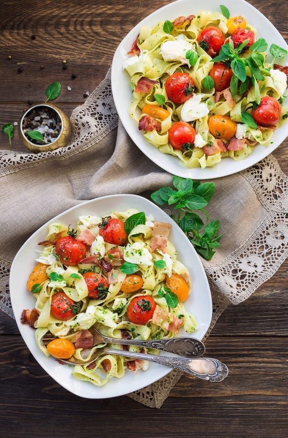 Макаронные изделия Fettuccine с испеченным сыром томатов, бекона и моццареллы стоковое изображение