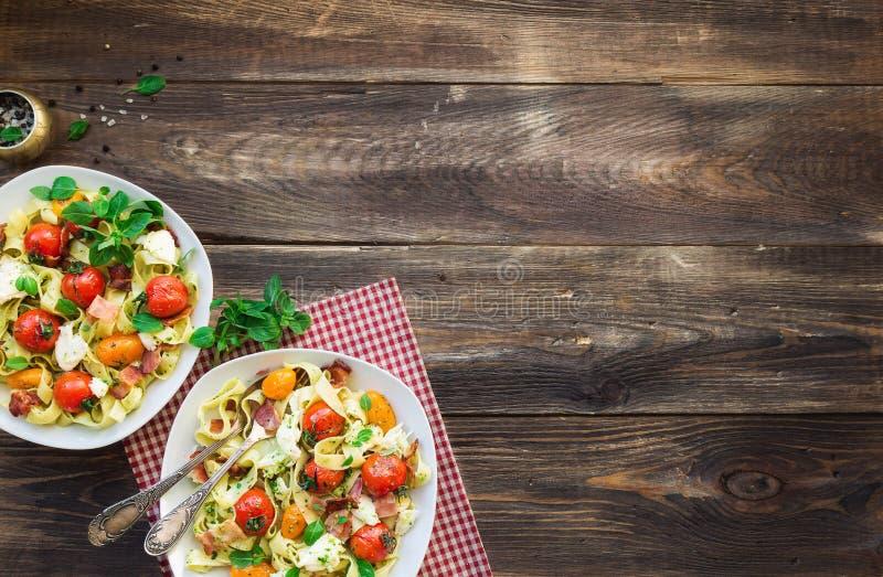 Макаронные изделия Fettuccine с испеченным сыром томатов, бекона и моццареллы стоковые изображения rf