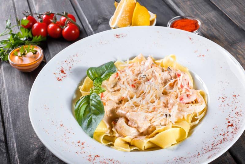 Макаронные изделия Fettuccine с морепродуктами, кальмаром звенят, креветка, мидии, устрицы, томат, сыр пармесан, базилик стоковая фотография