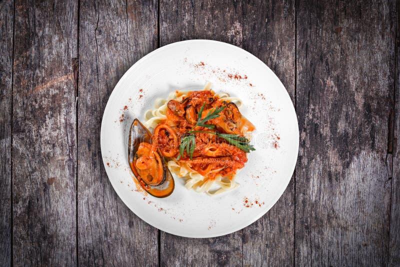Макаронные изделия Fettuccine с морепродуктами, мидиями, осьминогом, устрицами, томатным соусом и травами на деревянной предпосыл стоковые изображения