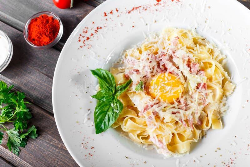 Макаронные изделия Fettuccine с мясом, ветчиной, яичком, сыр пармесаном, базиликом и cream соусом на плите стоковые изображения