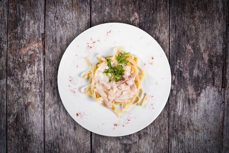Макаронные изделия Fettuccine с мясом, cream соусом и травами на плите на деревянной предпосылке стоковое изображение