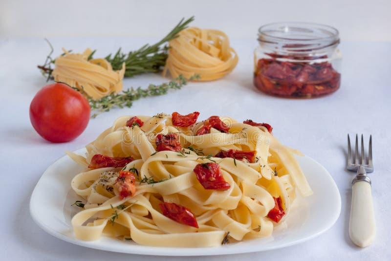 Макаронные изделия Fettuccine с солнц-высушенными томатами и различными травами стоковые фото
