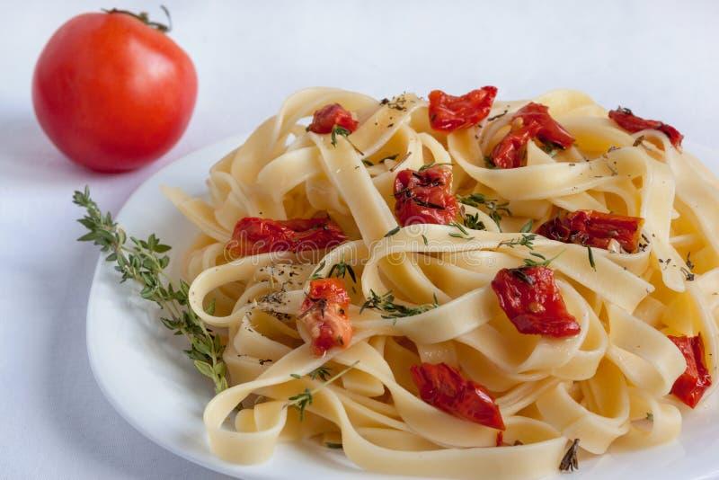 Макаронные изделия Fettuccine с солнц-высушенными томатами и розмариновым маслом лежат на белой плите стоковые изображения