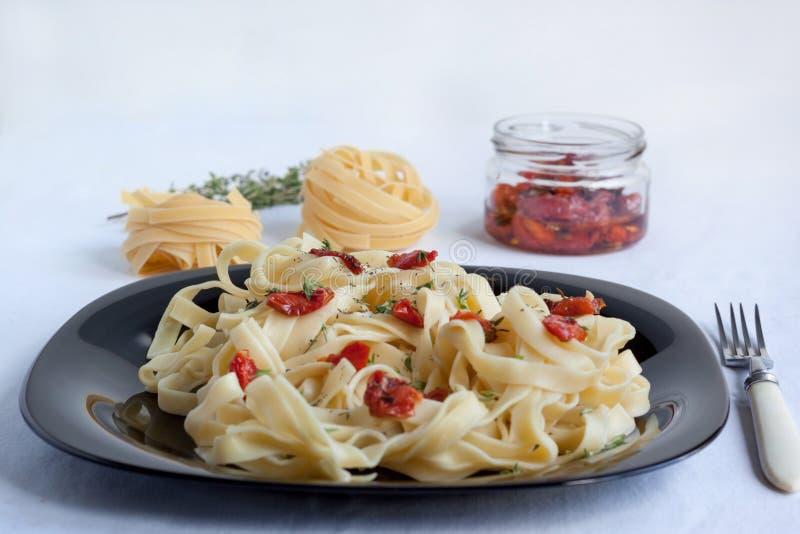 Макаронные изделия Fettuccine с солнц-высушенными томатами и розмариновым маслом лежат на черной плите стоковая фотография rf
