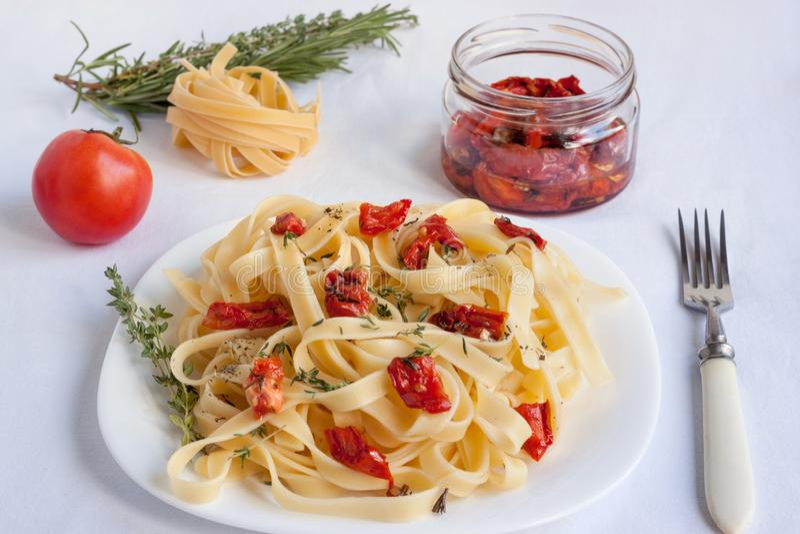 Макаронные изделия Fettuccine с солнц-высушенными томатами лежат на белой плите стоковые фотографии rf
