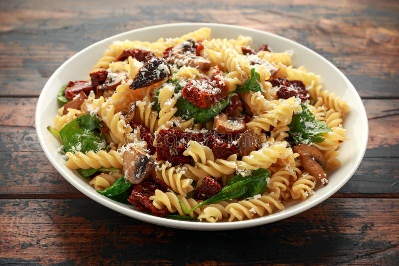 Макаронные изделия Fusilli с солнцем высушили томаты, грибы, сыр пармезан и шпинат E стоковое фото