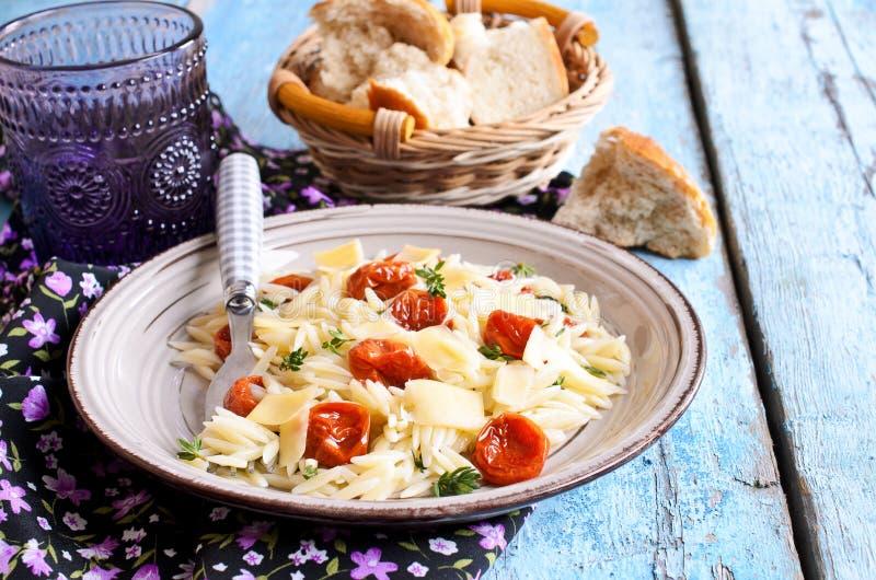 Макаронные изделия с солнцем высушили томаты, сыр и тимиан стоковая фотография