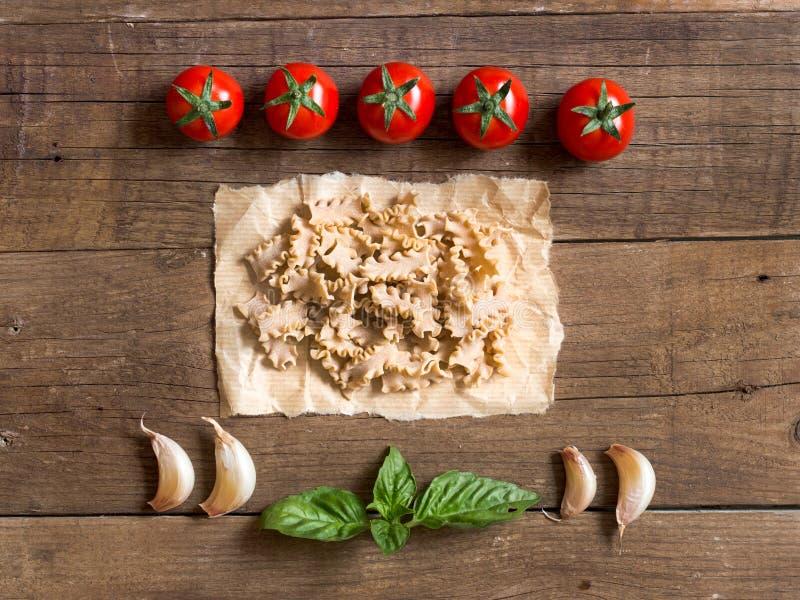Макаронные изделия, томаты, чеснок и базилик на деревянной предпосылке стоковое фото rf