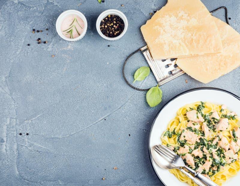 Макаронные изделия Tagliatelle с семгами, шпинатом и сметанообразным соусом, сыр пармесаном над конкретной текстурированной предп стоковые изображения