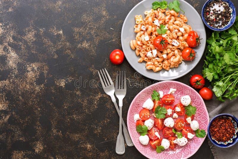 Макарон с соусом, салатом с томатом и сыром моццареллы Взгляд сверху, экземпляр космоса стоковое фото rf