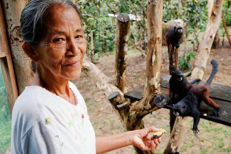 Македония, Амазония/Колумбия - 15-ое марта 2016: любимчик местной дамы члена племени ticuna подавая monkeys с бананами в ju тропи стоковое изображение rf