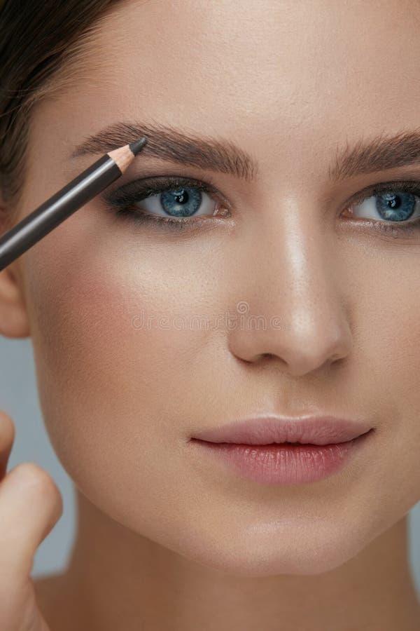 Макияж красоты Женщина формируя бровь с крупным планом карандаша чела стоковая фотография rf