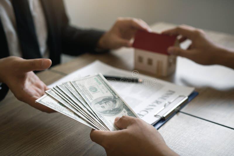 Маклеры внутренних продаж и инвесторы недвижимости обменивают с инвесторами храня наличные деньги на руке агента стоковая фотография rf