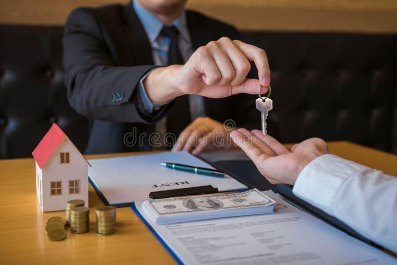 Маклеры дома продавца снабжают ключевое новые домовладельцы в офисе стоковые изображения rf