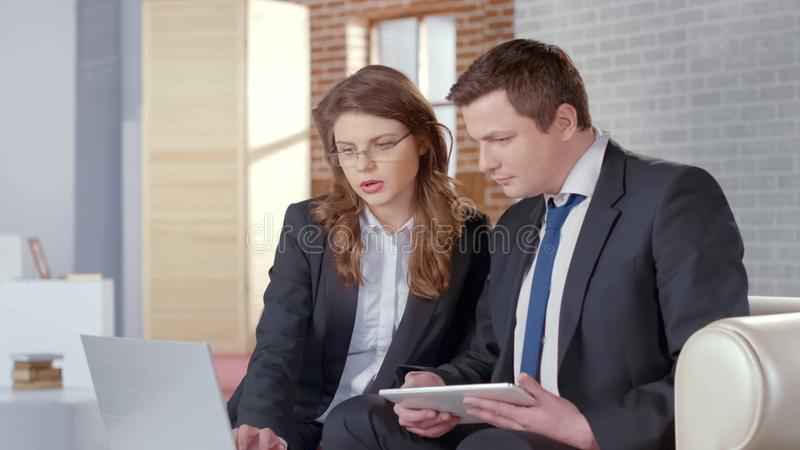 Маклер по операциям с недвижимостью показывая фото на ноутбуке, убеждая, что клиент купил свойство стоковые фото