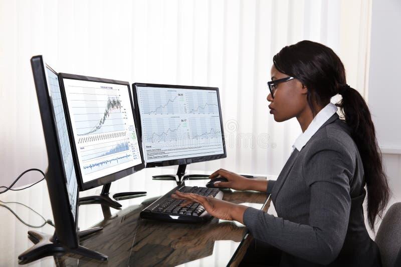 Маклер фондовой биржи работая на множественных компьютерах стоковое изображение rf