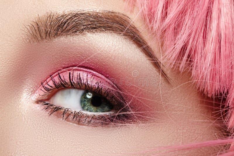 Макрос крупного плана розового макияжа глаза моды Выразительный макияж, яркие тени для век лета, волосы цвета мадженты, сияющая к стоковое фото