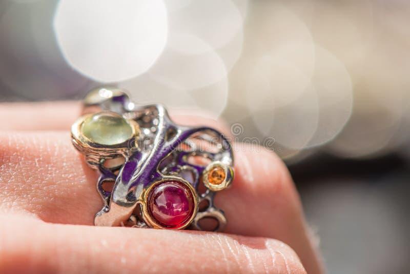 Макрос снял серебряного обручального кольца на красочной, сверкная предпосылке стоковые изображения rf