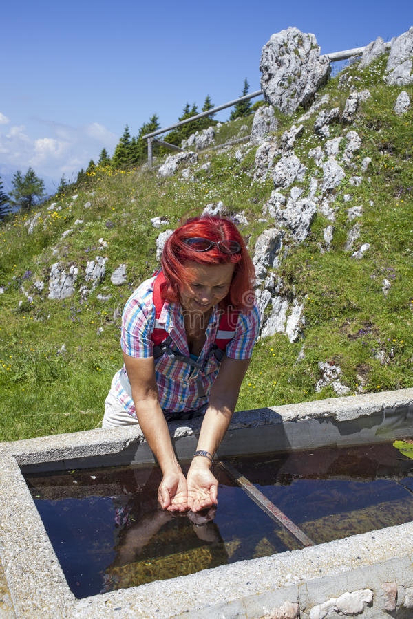 Максимум trekker женщины освежая в горах стоковые изображения
